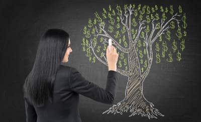 Brunette business woman is drawing a diagram on the chalk blackboard.